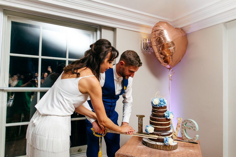 Bride and groom cutting wedding cake with sword