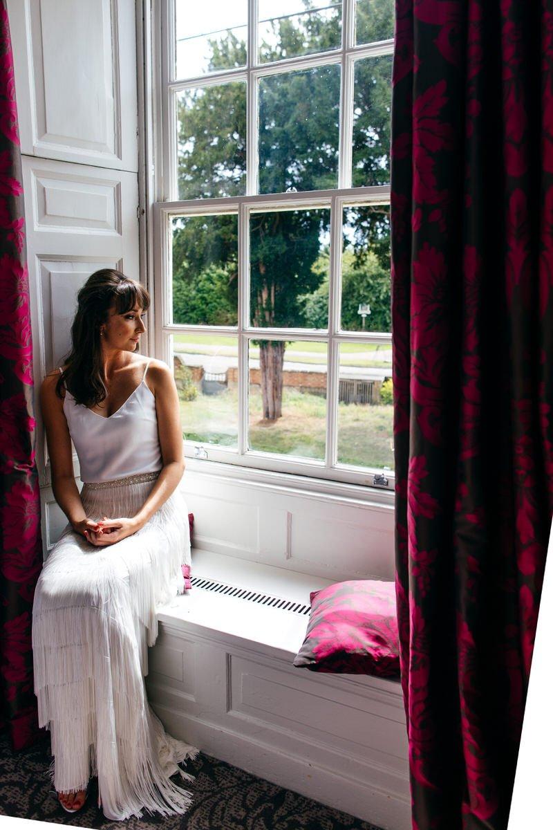 Bride sitting on window ledge at Barton Hall