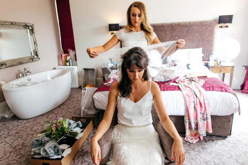 Bridesmaid helping bride put veil on