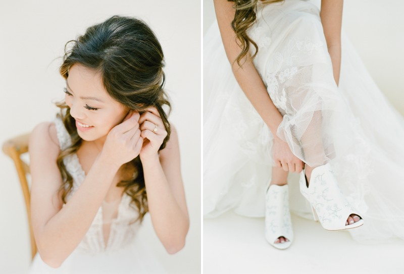 Bride putting on earrings and shoes