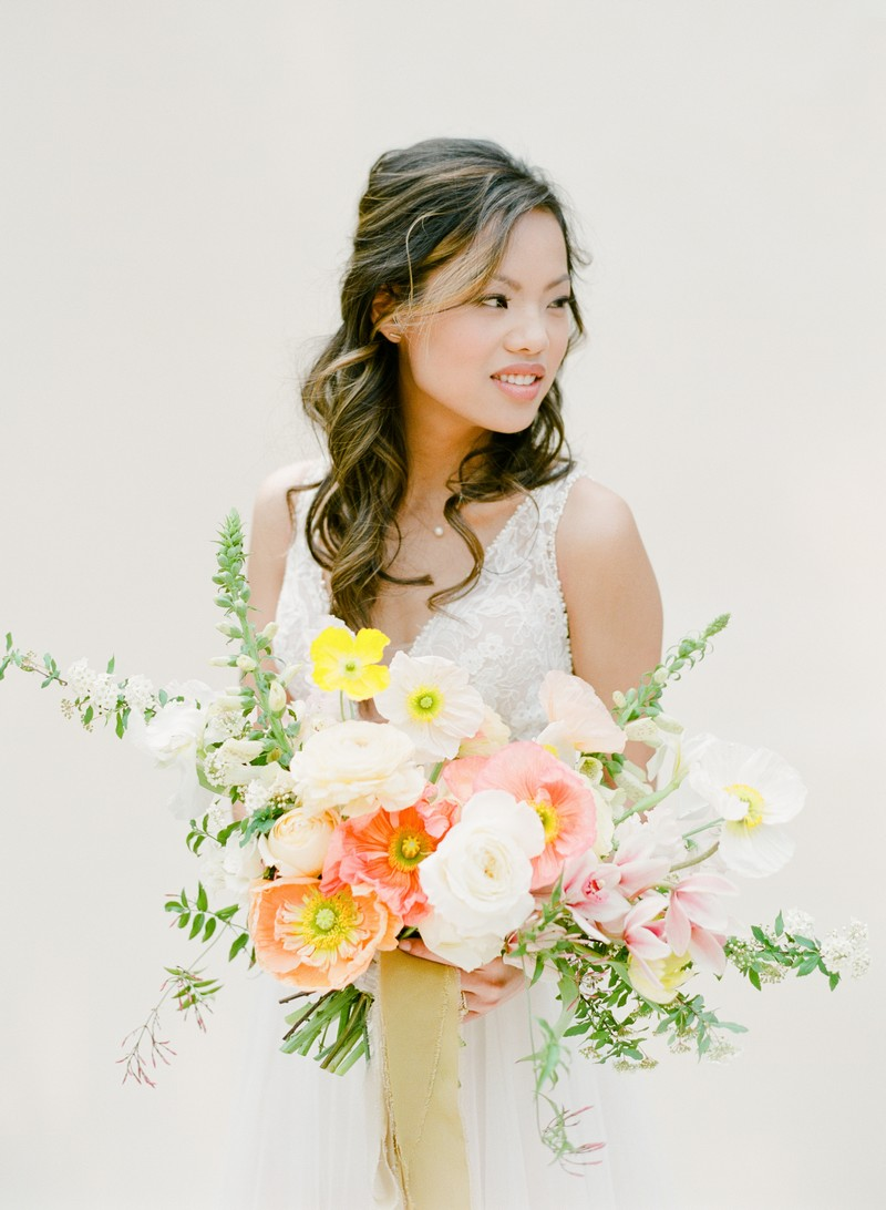 Bride holding colourful wedding bouquet with yellow and peach flowers