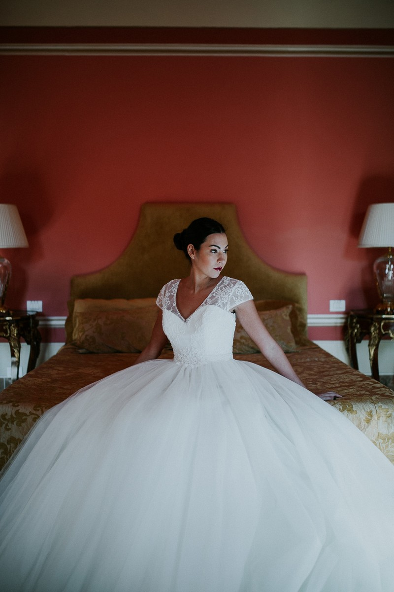 Bride sitting on bed in Villa Lenka, Tuscany