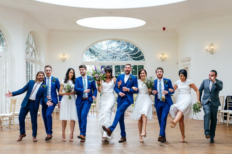 Bridal party dancing with arms linked at Barton Hall