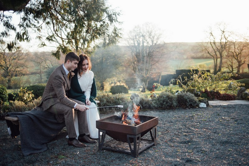 Bride and groom toasting marshmallows on fire