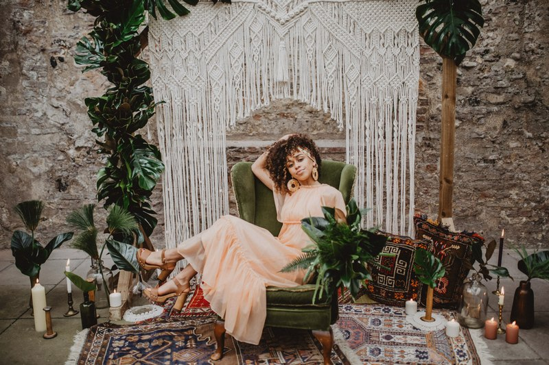 Bride sitting on chair in front of macramé wedding backdrop