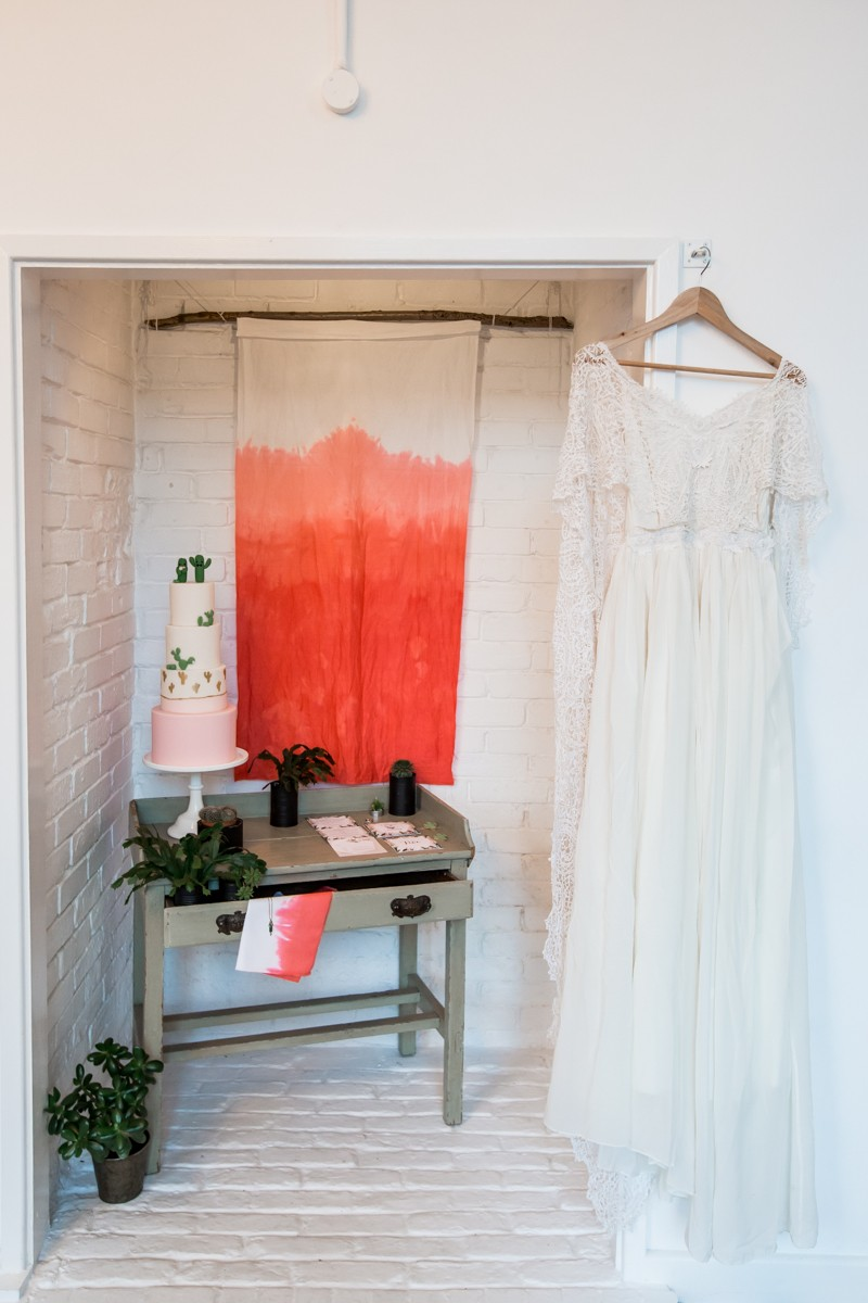 Wedding dress hanging by table with cactus wedding cake and stationery