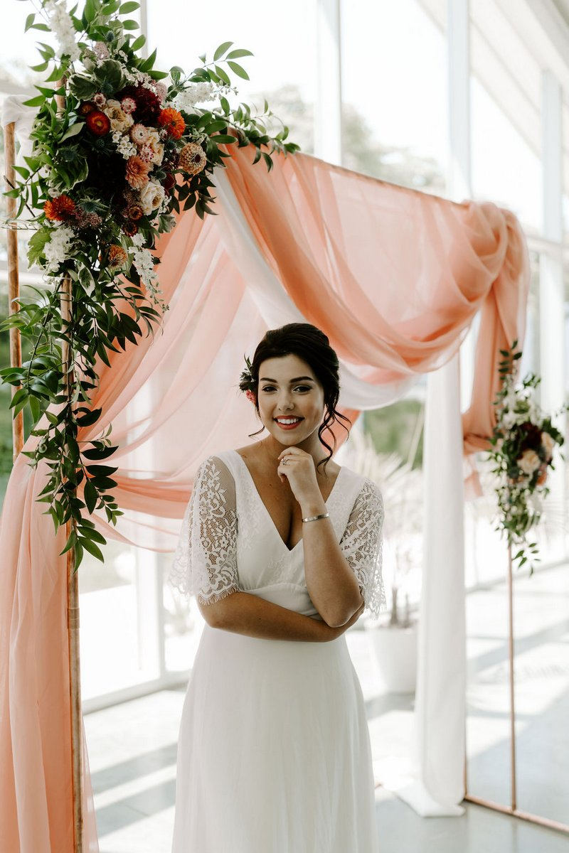 Bride standing in front of pink fabric backdrop
