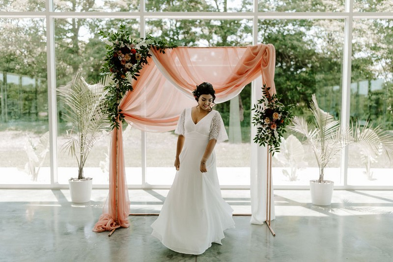 Bride standing in front of ceremony backdrop of pink fabric, foliage and flowers