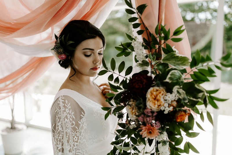 Bride standing by winter wedding floral display