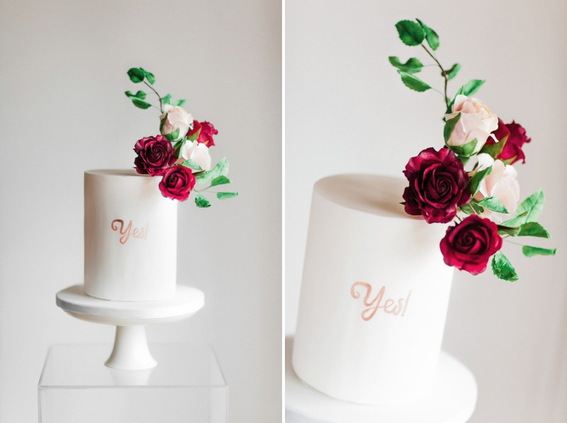 White engagement cake with 'yes' lettering and rose topper