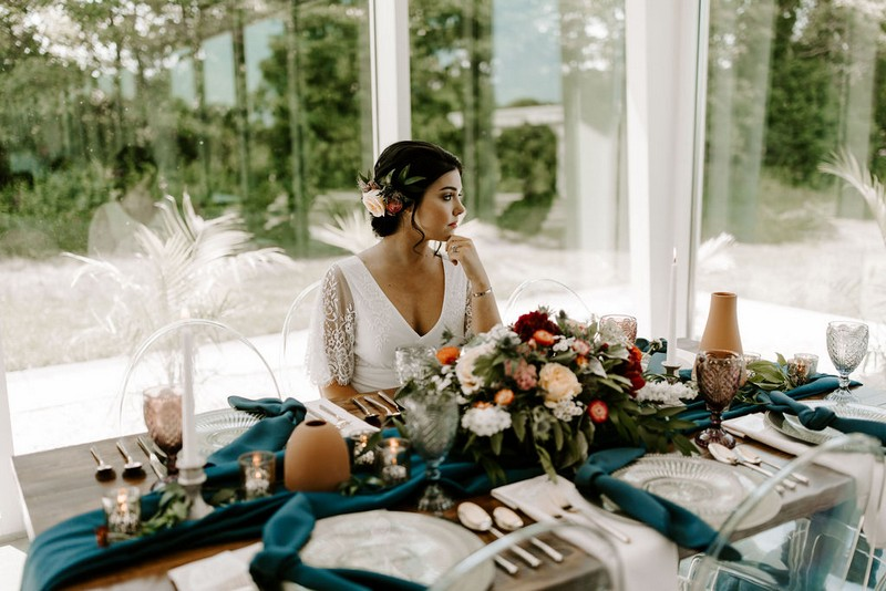 Bride sitting at winter wedding table with blue linen and natural styling