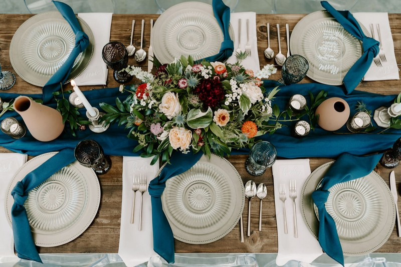 Winter wedding table with blue linen, glass plates and floral centrepiece
