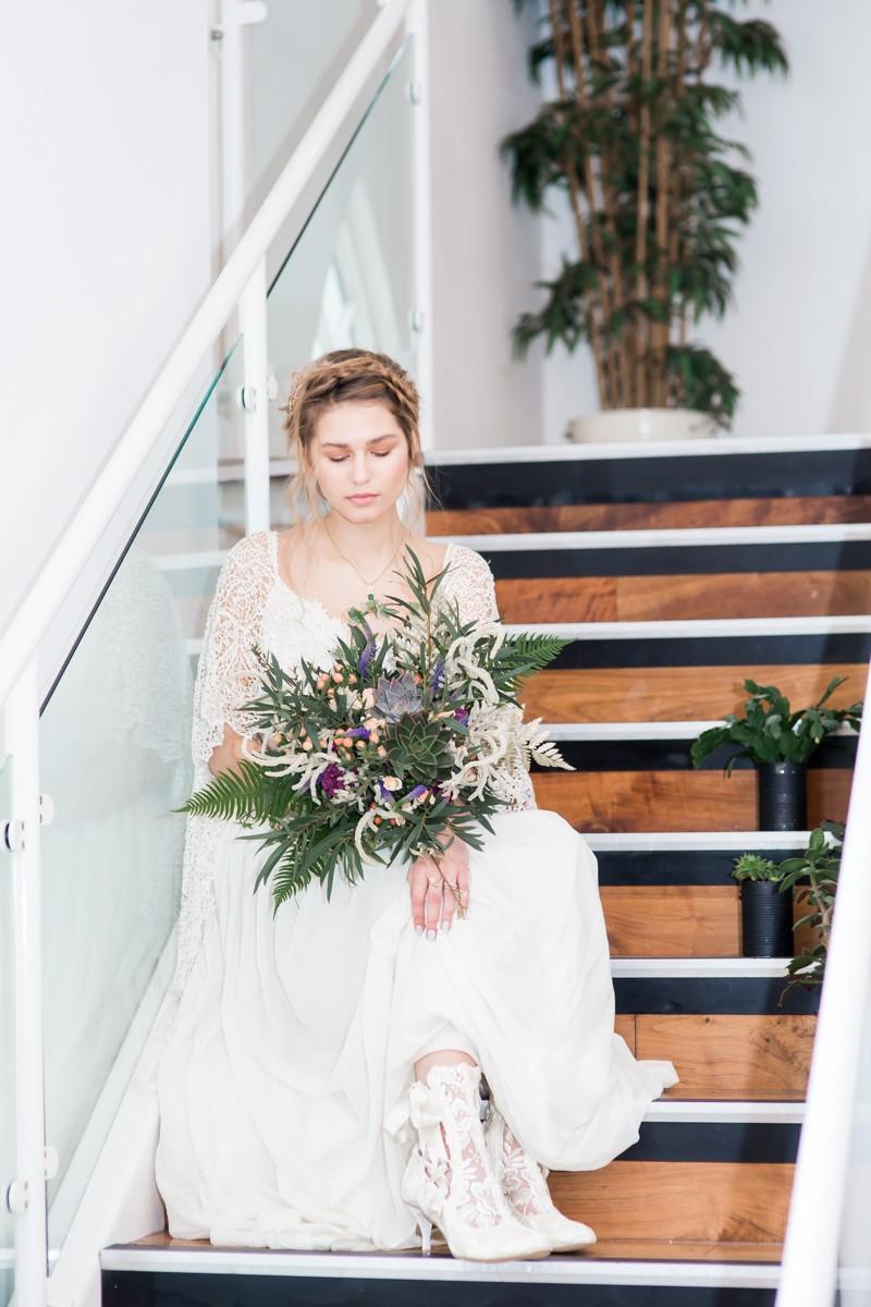 Bride sitting on steps holding bouquet