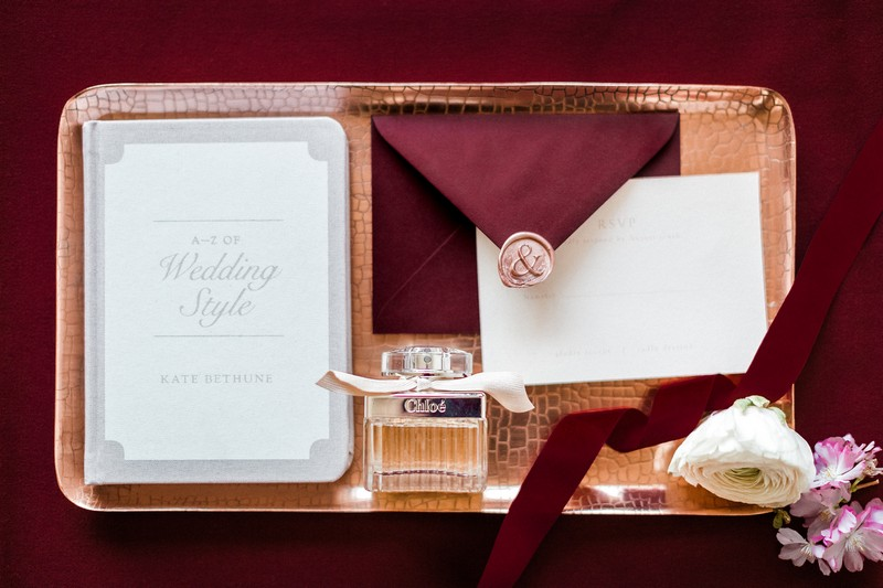 Engagement party invitation and perfume on rectangular tray