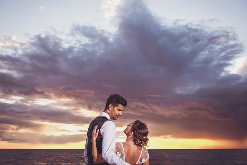 Bride and groom in front of clouds over the sea at sunset - Picture by AWPhotographic