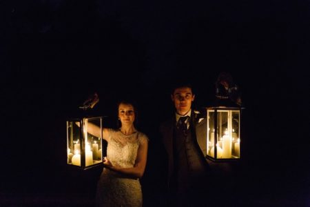 Bride and groom holding up candles in lanterns in the dark - Picture by Paul Joseph Photography