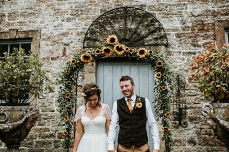 Bride and groom standing in front of sunflower arch - Picture by Ryan Goold Photography