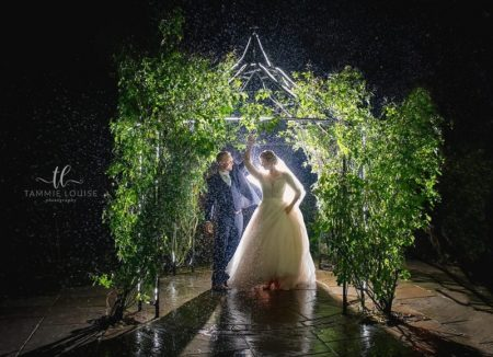 Bride and groom under foliage covered gazebo in rain at night - Picture by Tammie Louise Photography