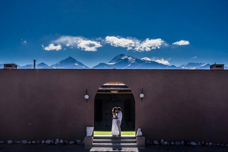 Bride and groom standing in arch opening in wall with mountains in background - Picture by Adrián Zussino Fotografía