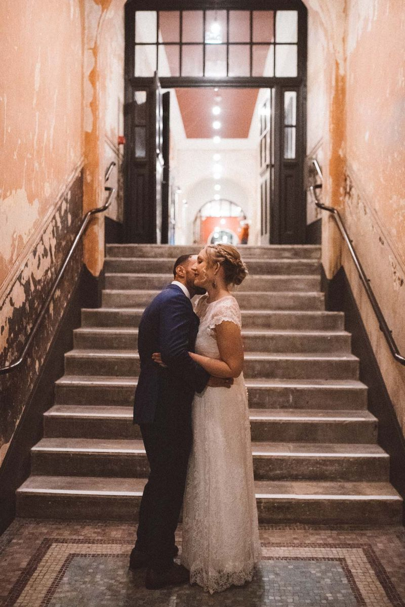 Groom kissing bride on the neck in corridor in front of steps - Picture by Barbara K. Photography