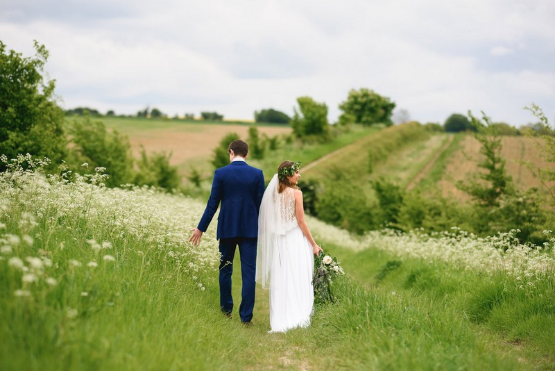Bride and groom walking in countryside - Picture by Sam Gibson Photography