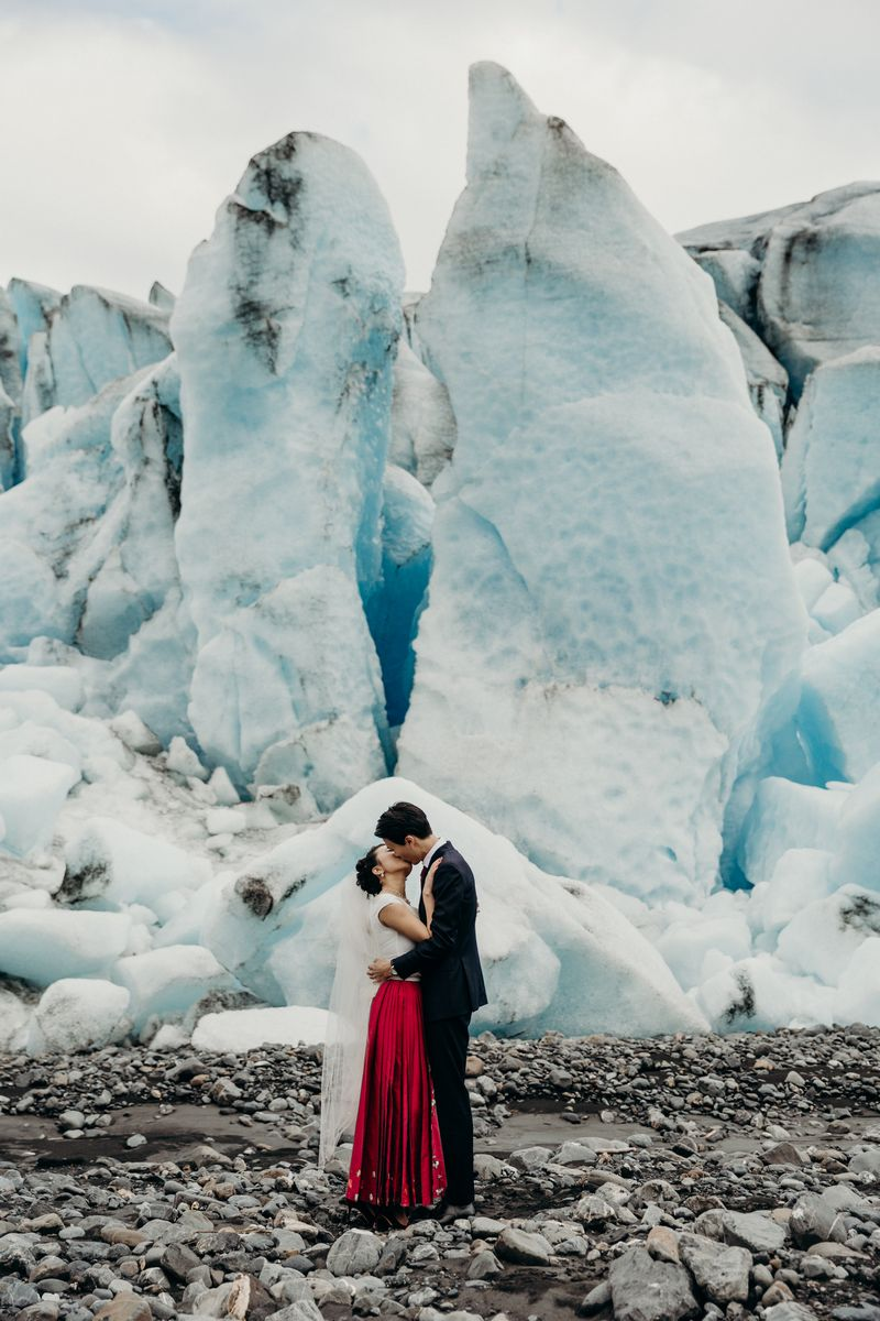 Bride and groom kissing in front of glacier - Picture by Kristian Irey Photography
