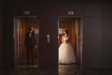 Bride and groom standing next to each other in separate lifts - Picture by Katja & Simon Photography