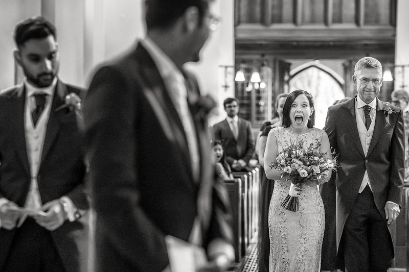 Bride pulling excited face at groom as she walks down the aisle towards him - Picture by Rafe Abrook Photography