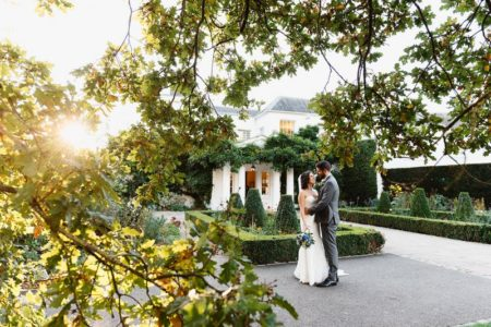 Picture of bride and groom in courtyard of wedding venue taken through tree branches - Picture by Fiona Kelly Photography