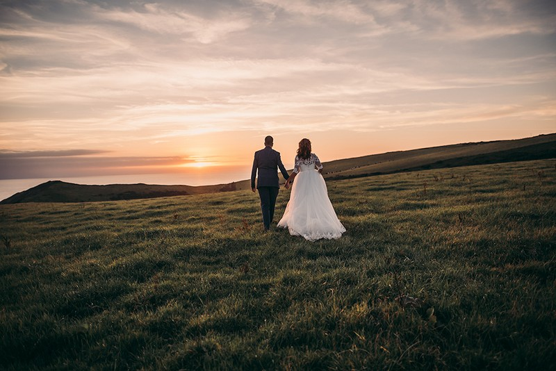 Bride and groom holding hands as they walk across field towards sunset - Picture by Tracey Warbey Photography