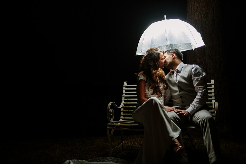Bride and groom on bench kissing under lit umbrella in the dark - Picture by Nisha Haq Photography