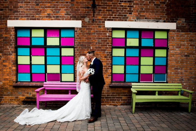 Bride and groom kissing between brightly coloued tiled windows - Picture by Nicola Norton Photography
