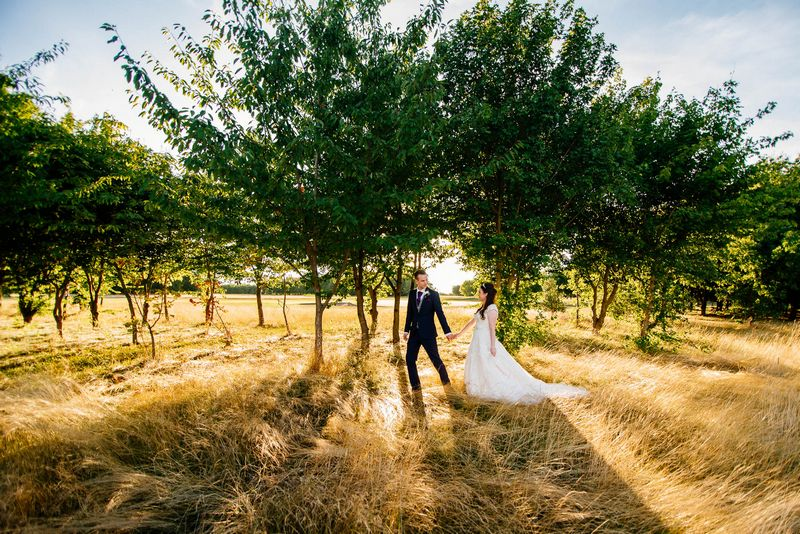 Bride and groom holding hands as they walk past trees - Picture by Ufniak Photography
