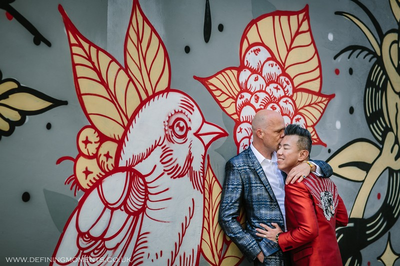 Man kissing husband's head against bird graffiti wall - Picture by Defining Moments Photography