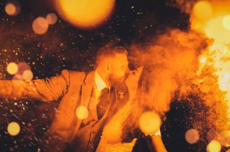 Bride and groom kissing amongst smoke and sparks from flares - Picture by Lilly Sells Photography