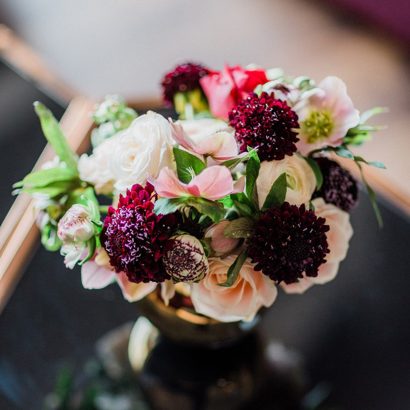 Small vase of pink and dark red flowers