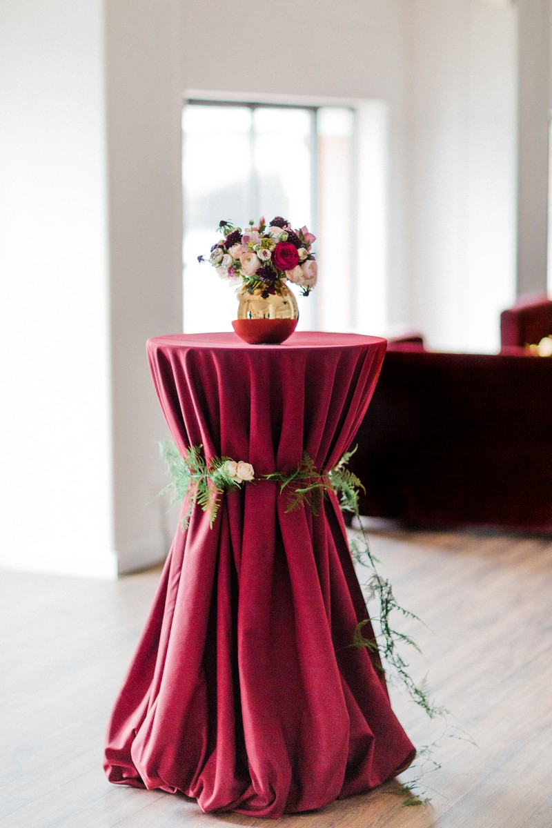 Vase of flowers on small table covered with red tablecloth and wrapped in foliage