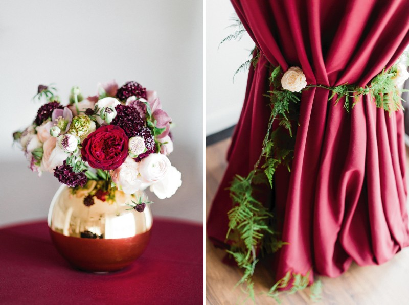 Small metallic vase of flowers and foliage wrapped around tablecloth