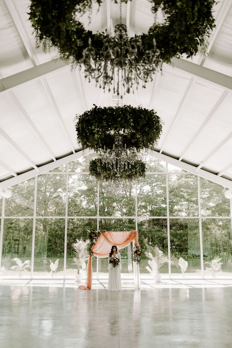 Bride standing in front of backdrop with hanging foliage installations overhead