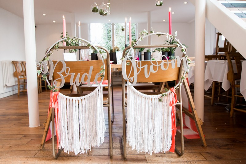 Wedding chairs with bride and groom hoops on the back