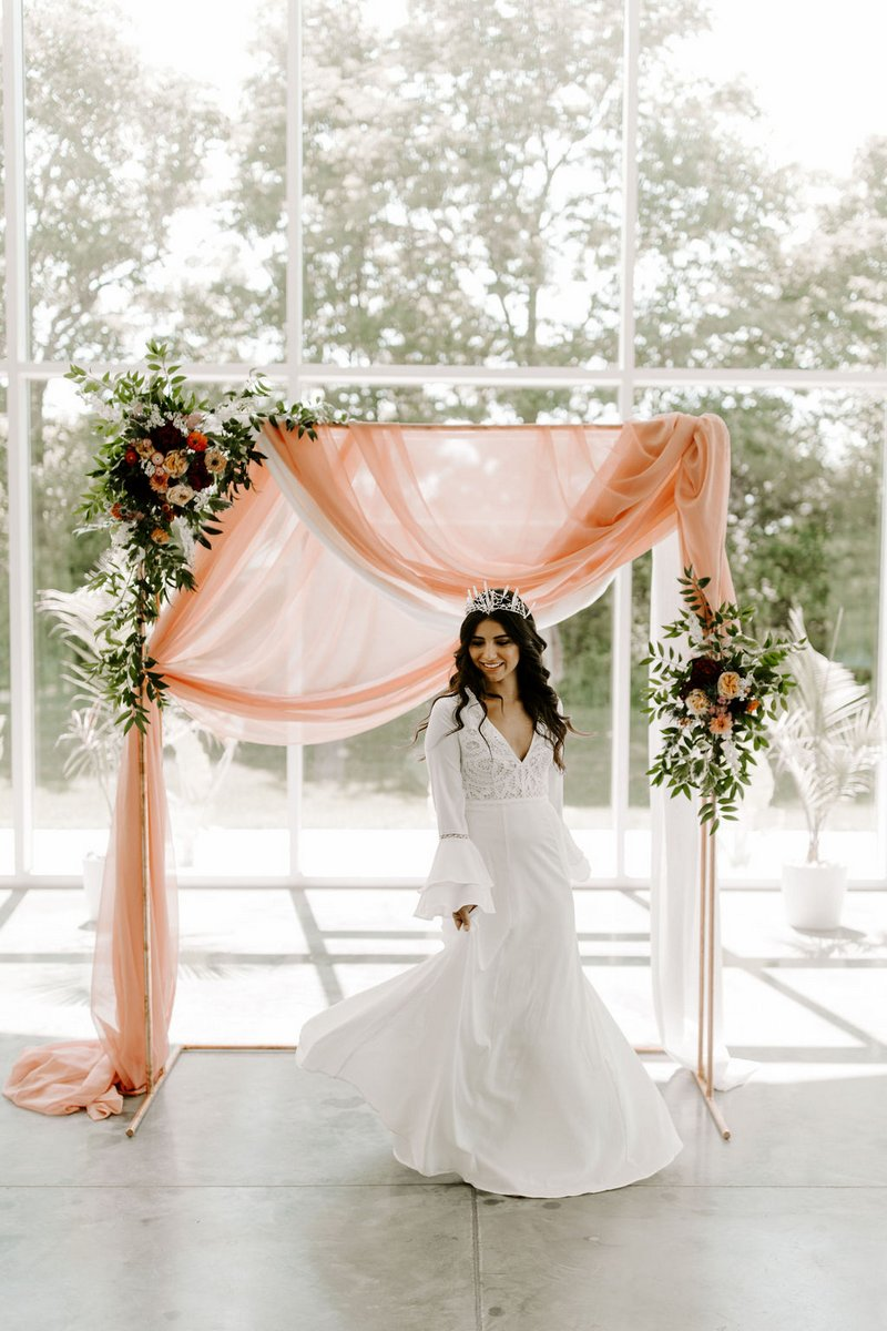 Bride standing in front of pink fabric ceremony backdrop