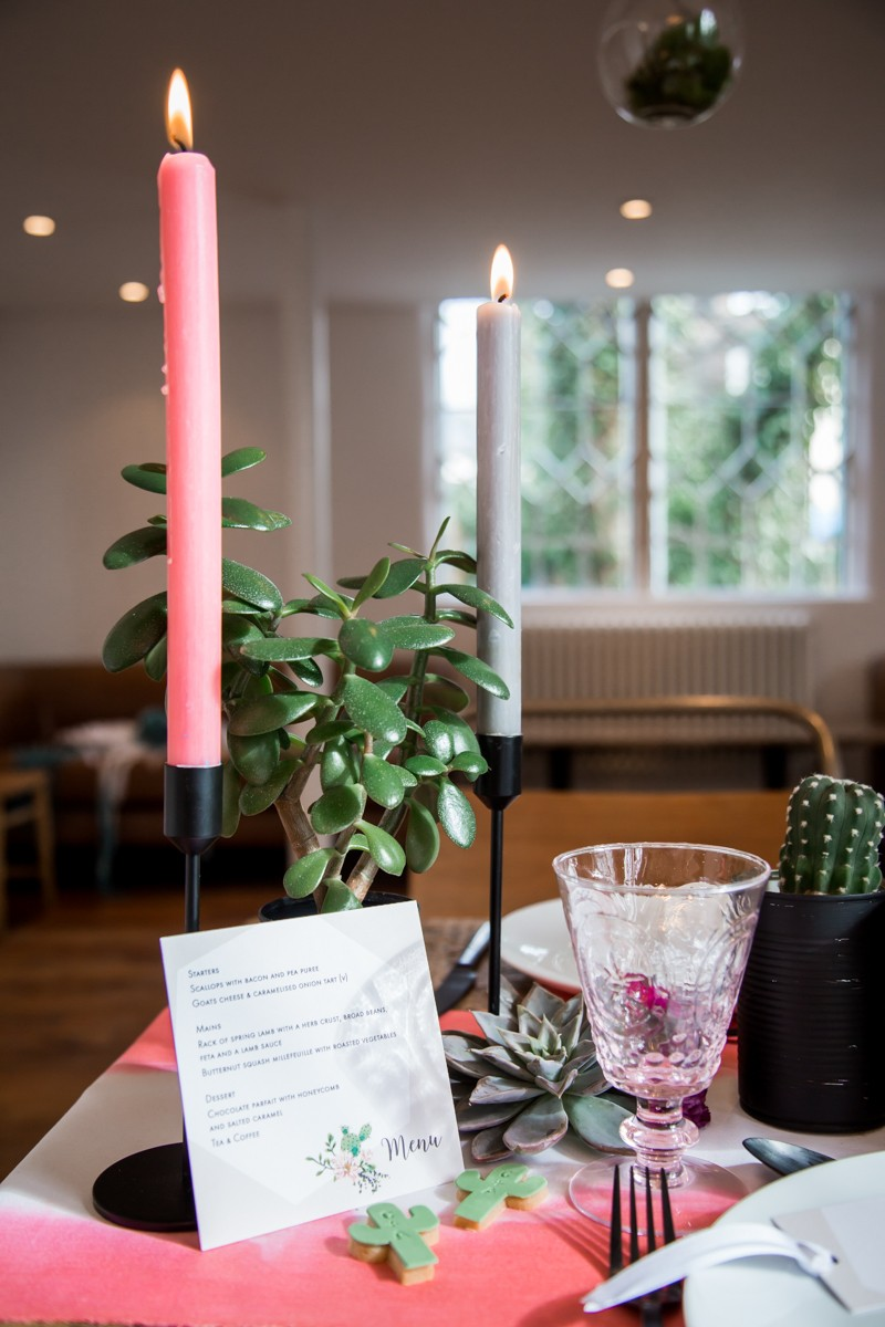 Pink and grey candles on wedding table with cactus plants