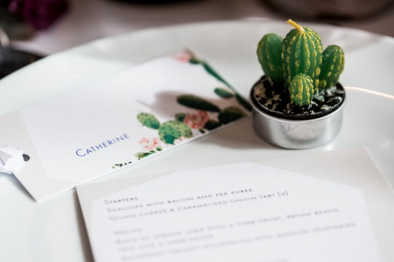 Small cactus plant and cactus name tag at wedding place setting