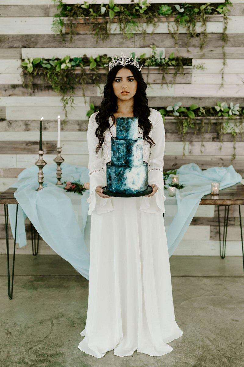 Bride holding blue celestial style wedding cake