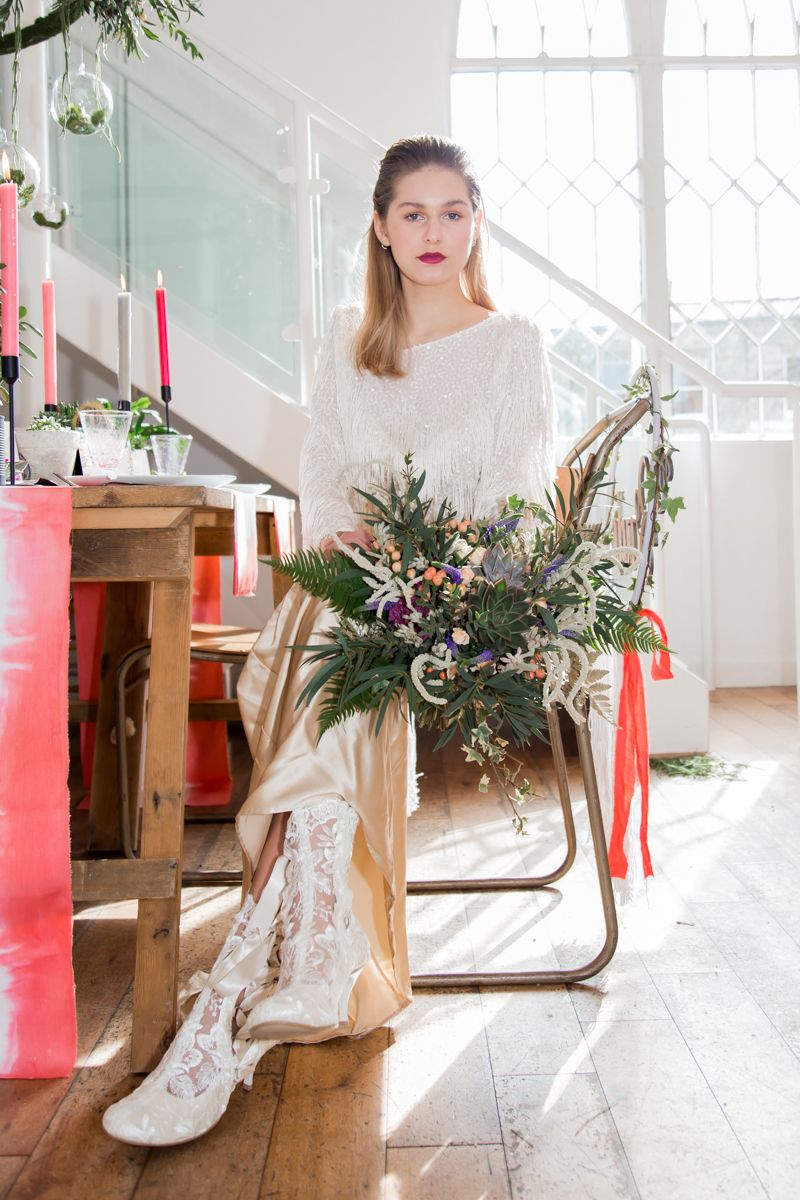 Bride sitting at wedding table holding bouquet