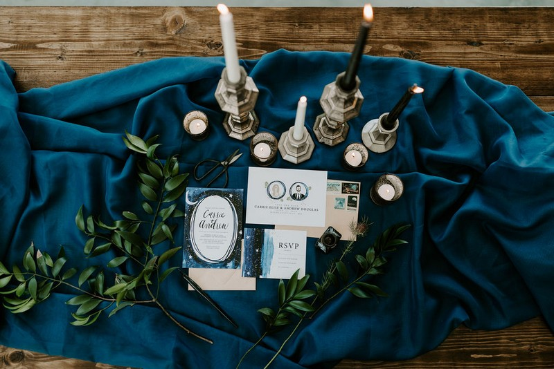 Blue celestial wedding stationery and candles on blue cloth