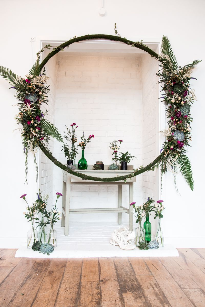 Wedding ceremony display with floral hoop and vases of flowers