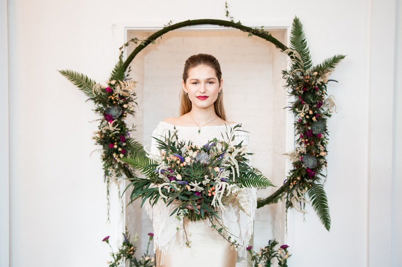 Bride holding bouquet in front of floral hoop