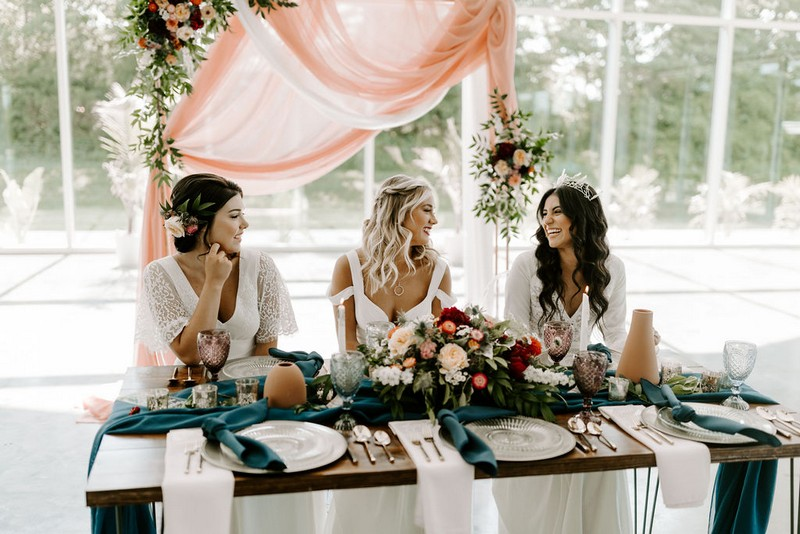 Three brides sitting at winter wedding table