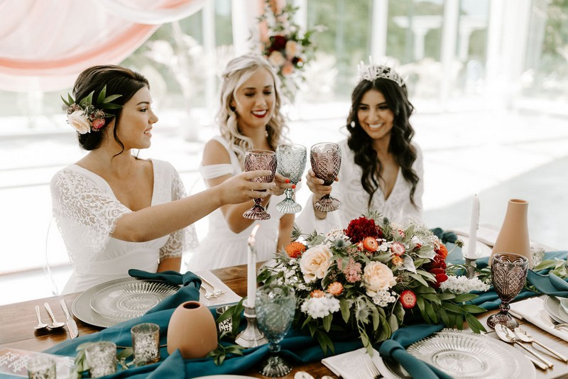 Three brides toasting at wedding table